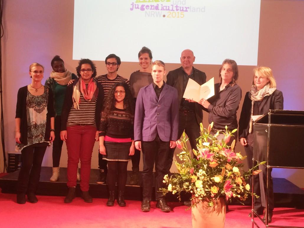 Die Preisverleihung am 9. Dezember im Landestheater Neuss: Thomas Richhardt, der Leiter des Projekts, hält die Preisurkunde hoch.